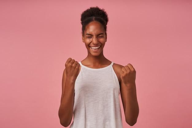 Jovem mulher de cabelos castanhos, de aparência agradável e muito feliz, regozijando-se com os olhos fechados e levantando emocionalmente as mãos, posando sobre uma parede rosa