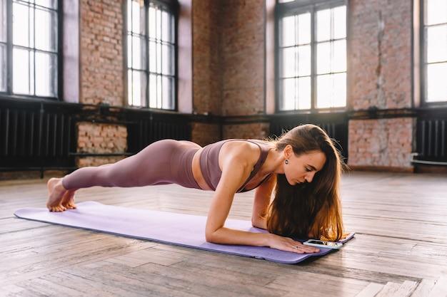 Jovem mulher de cabelos compridos fazer complexo de alongamento de asanas de ioga em aula de sol de estilo loft usando seu smartphone. aulas e treinamento online.