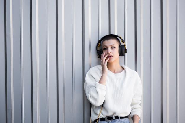 Jovem mulher de cabelos curtos que escuta a música ao olhar a câmera