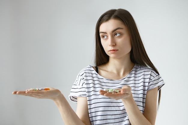 Jovem mulher de cabelos escuros hesitante não consegue decidir entre remédios e vitaminas