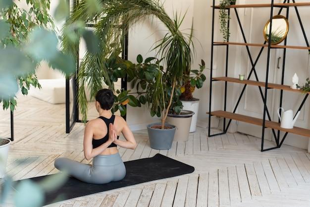 Jovem mulher de cabelos escuros praticando ioga pela manhã em sua casa perto de plantas.