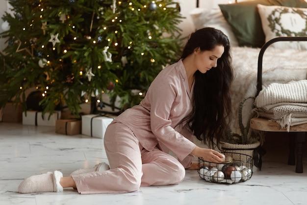 Jovem mulher de cabelos escuros, vestindo um pijama da moda, segurando as decorações de natal e posando ao lado da árvore de natal em casa.