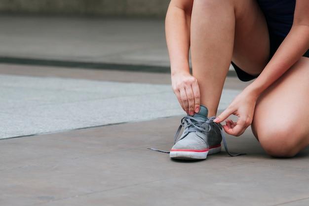 Jovem mulher de calçado de tênis esporte ajoelhou-se a fazer o cadarço. pronto para tênis de corrida em pessoa de corrida de exercício de esporte. feche as mãos amarrar os cadarços do corredor no estilo de vida de pessoa saudável de ginásio de fitness.