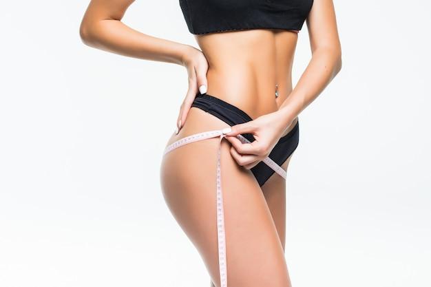Jovem mulher de calcinha preta medindo a cintura com fita métrica.