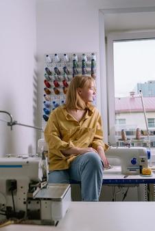 Jovem mulher de camisa amarela sentada em sua oficina de costura em frente aos fios coloridos e máquinas de costura, foco seletivo
