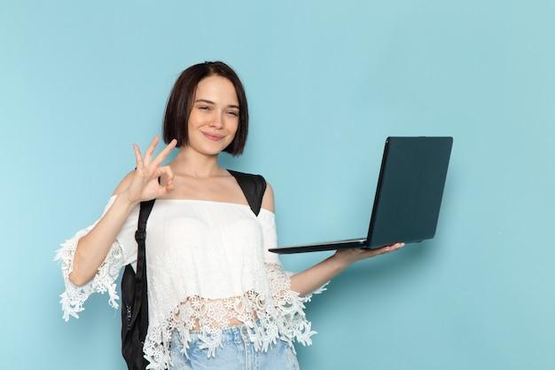 Jovem mulher de camisa branca e bolsa preta segurando e usando laptop sorrindo no azul