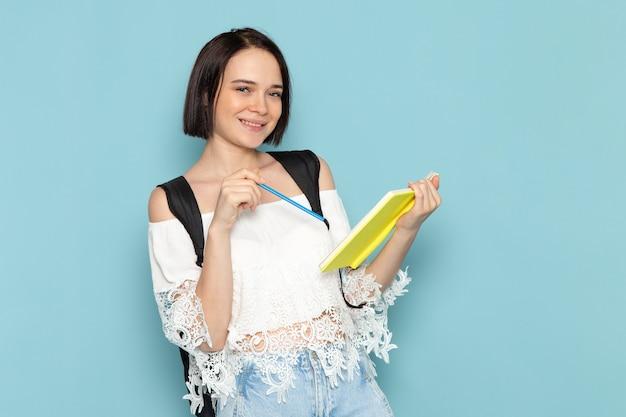 Jovem mulher de camisa branca e bolsa preta segurando o caderno azul