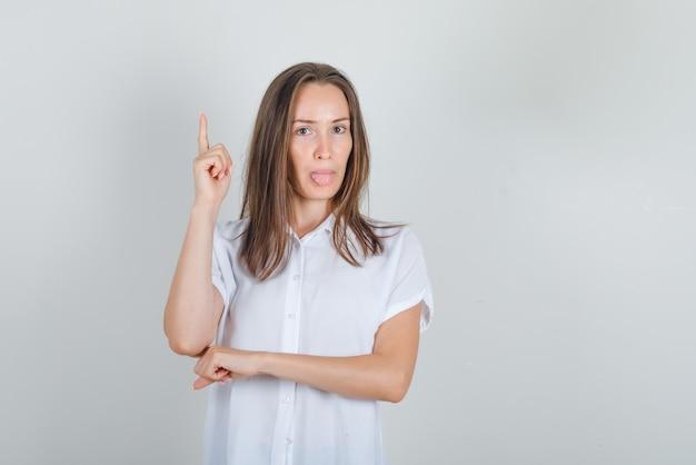 Jovem mulher de camisa branca, mostrando a língua com o dedo para cima
