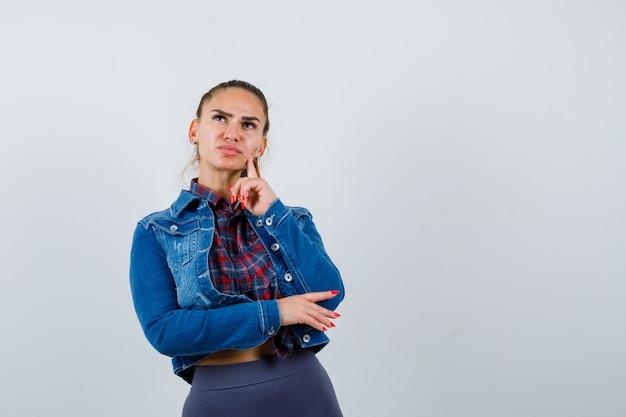 Jovem mulher de camisa quadriculada, jaqueta jeans em pé na pose de pensamento e parecendo sensata, vista frontal.