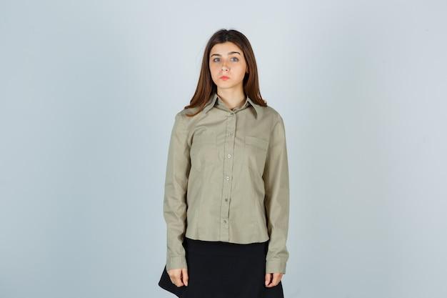 Jovem mulher de camisa, saia, olhando para a câmera e parecendo desapontada