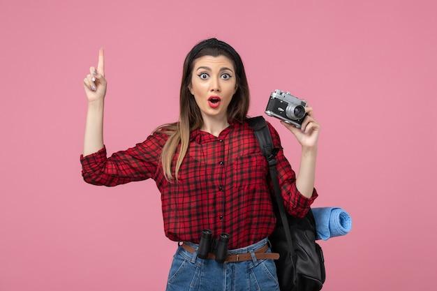 Jovem mulher de camisa vermelha com câmera no fundo rosa foto modelo mulher de frente