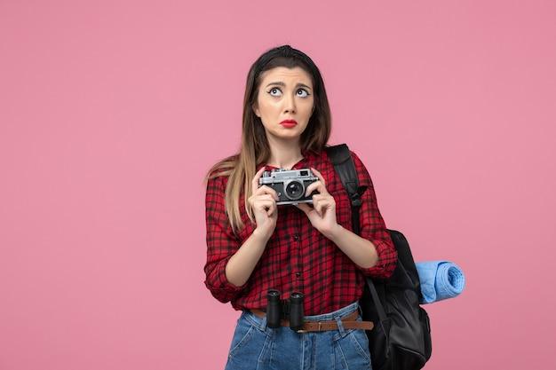 Jovem mulher de camisa vermelha com câmera no fundo rosa modelo foto mulher de frente