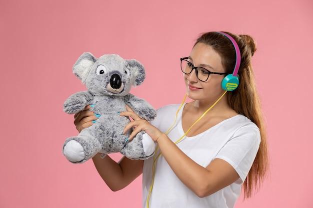 Jovem mulher de camiseta branca, de frente, ouvindo música com fones de ouvido e segurando um brinquedo fofo no fundo rosa