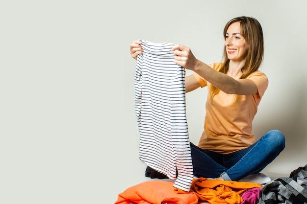 Jovem mulher de camiseta e calça jeans escolhe as coisas enquanto está sentado no chão, sobre um fundo claro