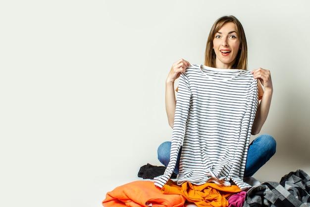 Jovem mulher de camiseta e calça jeans escolhe coisas do guarda-roupa enquanto está sentado no chão