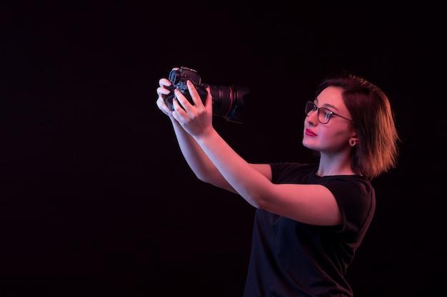 Jovem mulher de camiseta preta com câmera