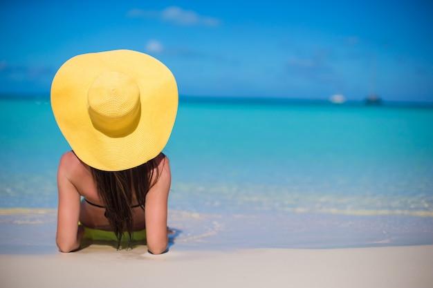 Jovem mulher de chapéu na praia desfrutar de férias nas caraíbas