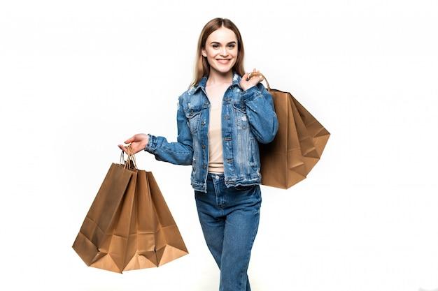 Jovem mulher de compra que guarda os sacos, isolados na parede cinzenta do estúdio.