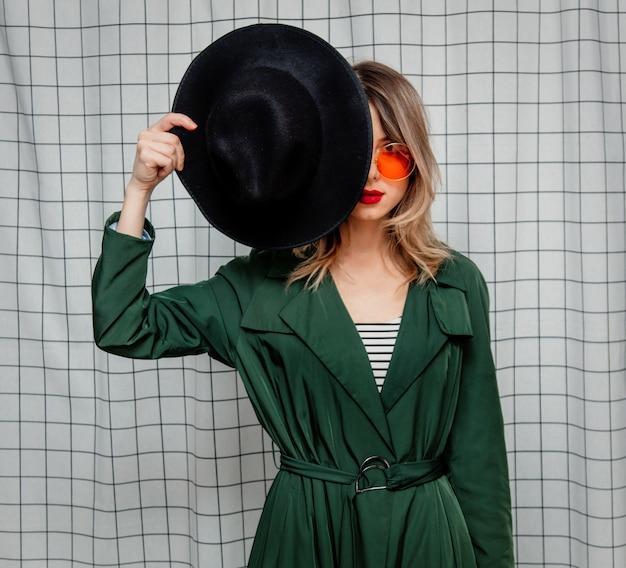 Jovem mulher de estilo em óculos escuros e capa verde no estilo dos anos 90