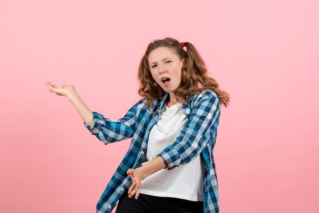 Jovem mulher de frente, com camisa quadriculada azul dançando na parede rosa jovem modelo emoções mulher criança menina