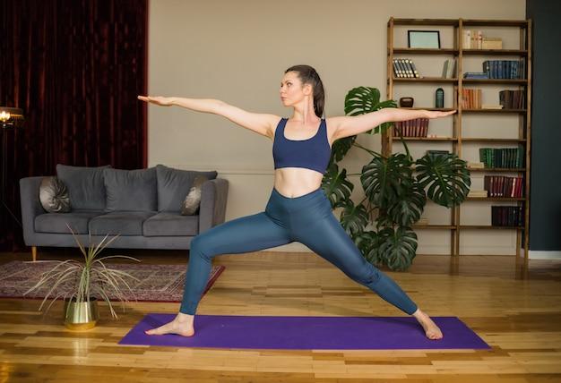 Jovem mulher de ioga em uniforme esportivo faz a pose de virabhadrasana em uma esteira de ioga na sala