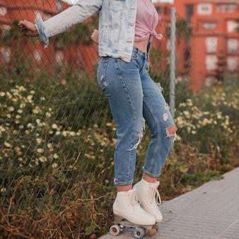 Jovem mulher de lado usando patim de rolo perto da cerca