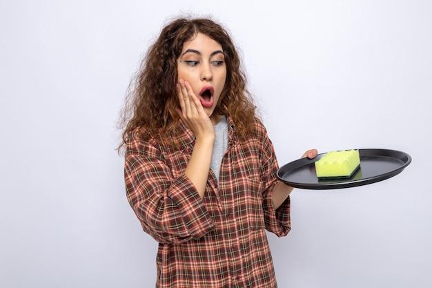 Jovem mulher de limpeza segurando e olhando para a esponja de limpeza na bandeja com medo de colocar a mão na bochecha