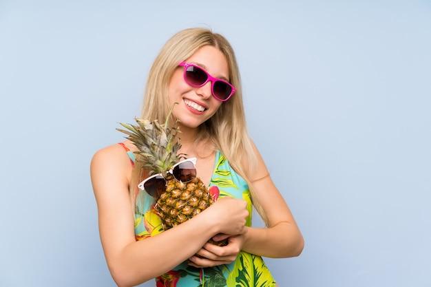 Jovem mulher de maiô segurando um abacaxi com óculos de sol