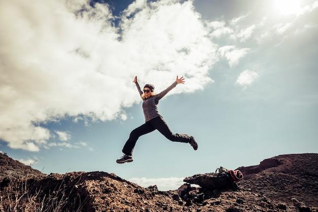 Jovem mulher de meia-idade pula para as pedras pelo conceito de felicidade e sucesso durante uma viagem de trekking turístico - conceito de liberdade e pessoas modernas em atividades de lazer ao ar livre
