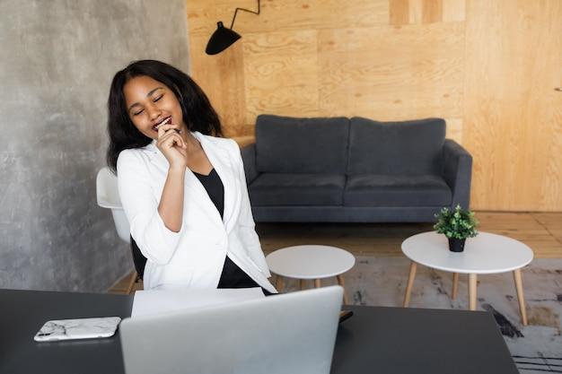 Jovem mulher de negócios africana focada no estudo on-line, assistindo ao podcast do webinar no laptop, ouvindo, aprendizagem, educação, curso, conferência, chamada, fazer anotações, sentar na mesa de trabalho