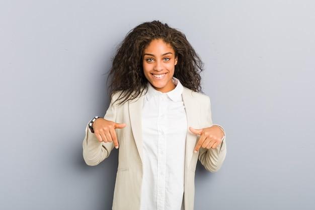 Jovem mulher de negócios afro-americana aponta para baixo com os dedos, sentimento positivo.
