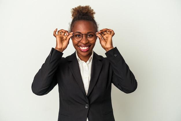 Jovem mulher de negócios afro-americana isolada no fundo branco, mostrando sinal de aprovação sobre os olhos