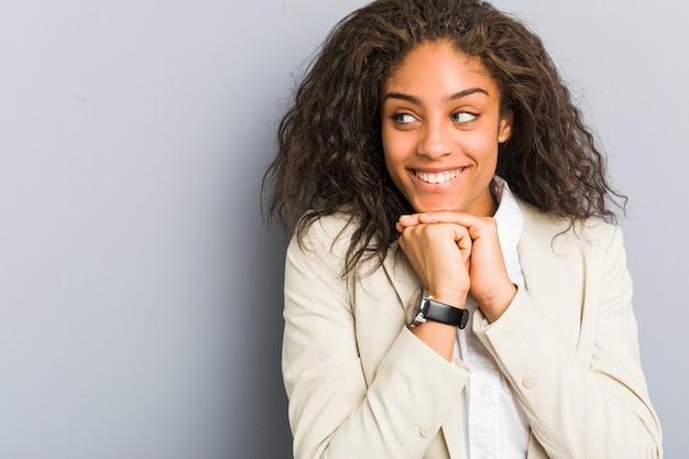 Jovem mulher de negócios afro-americana mantém as mãos sob o queixo, olhando alegremente para o lado.