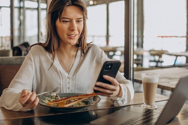 Jovem mulher de negócios almoçando em um café e trabalhando no computador
