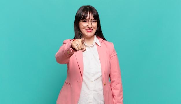Jovem mulher de negócios apontando para a câmera com um sorriso satisfeito, confiante e amigável, escolhendo você