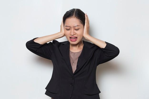 Jovem mulher de negócios asiática a tapar os ouvidos