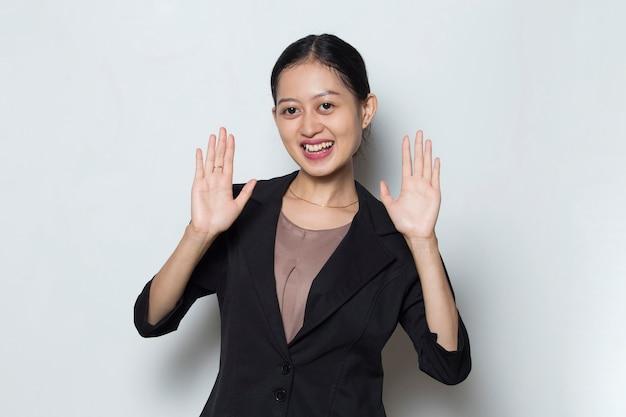 Jovem mulher de negócios asiática dando as boas-vindas a um gesto de convidados em fundo branco