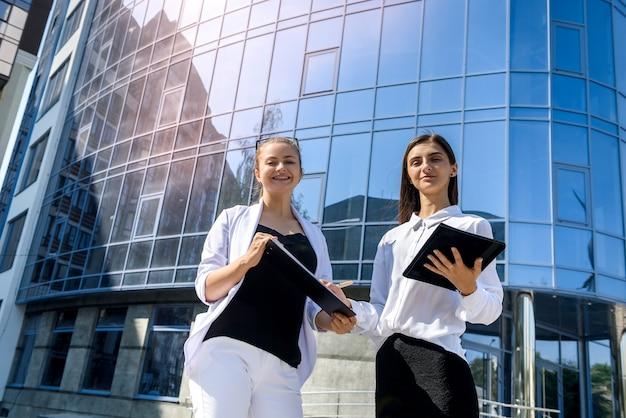 Jovem mulher de negócios assinando contrato fora do centro de negócios na cidade grande