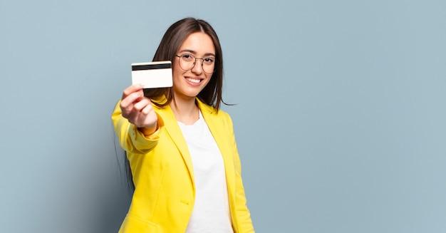 Jovem mulher de negócios bonita com cartão de crédito