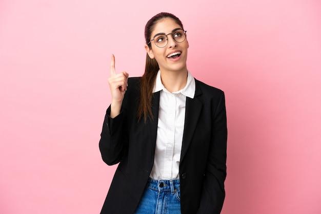 Jovem mulher de negócios caucasiana isolada em um fundo rosa apontando para cima e surpresa
