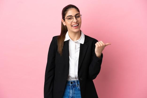 Jovem mulher de negócios caucasiana isolada em um fundo rosa apontando para o lado para apresentar um produto