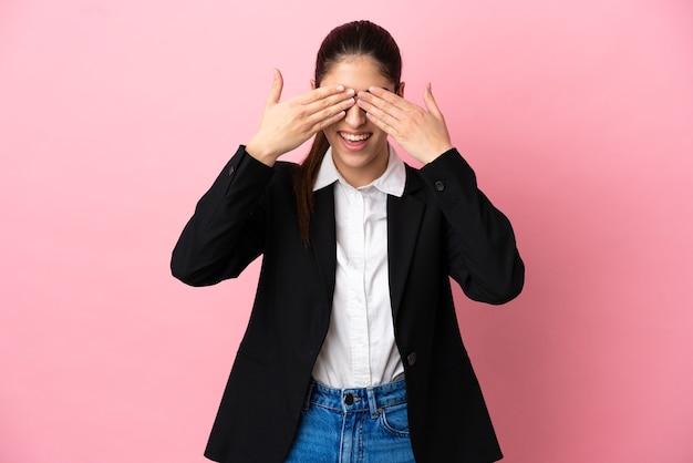 Jovem mulher de negócios caucasiana isolada em um fundo rosa cobrindo os olhos com as mãos