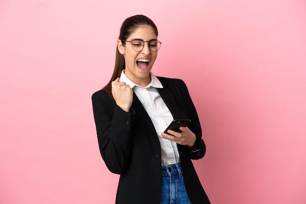 Jovem mulher de negócios caucasiana isolada em um fundo rosa com o telefone em posição de vitória