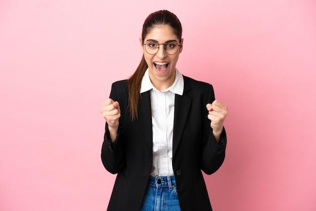 Jovem mulher de negócios caucasiana isolada em um fundo rosa comemorando uma vitória na posição de vencedora
