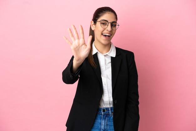 Jovem mulher de negócios caucasiana isolada em um fundo rosa contando cinco com os dedos