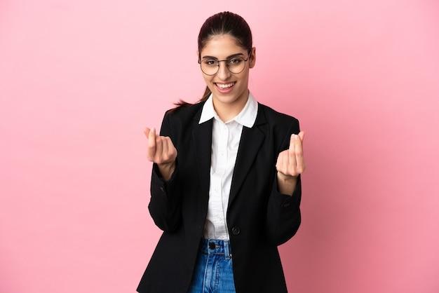 Jovem mulher de negócios caucasiana isolada em um fundo rosa fazendo gesto de dinheiro