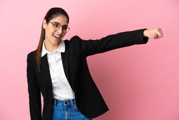 Jovem mulher de negócios caucasiana isolada em um fundo rosa fazendo um gesto de polegar para cima