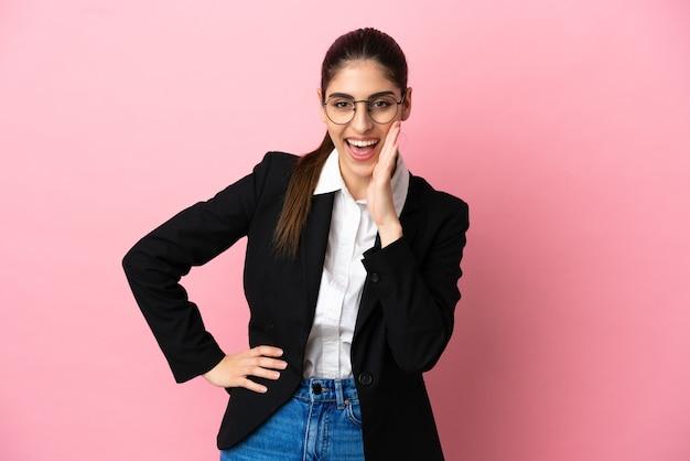 Jovem mulher de negócios caucasiana isolada em um fundo rosa gritando com a boca bem aberta