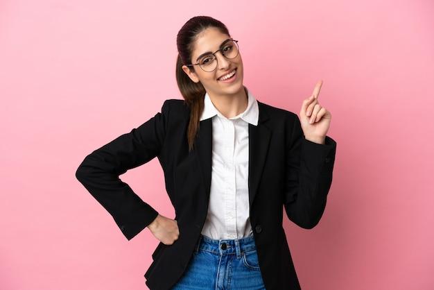 Jovem mulher de negócios caucasiana isolada em um fundo rosa mostrando e levantando um dedo em sinal dos melhores