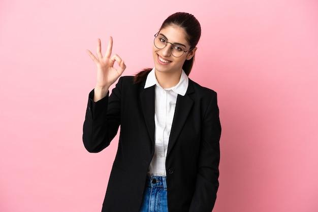 Jovem mulher de negócios caucasiana isolada em um fundo rosa mostrando sinal de ok com os dedos